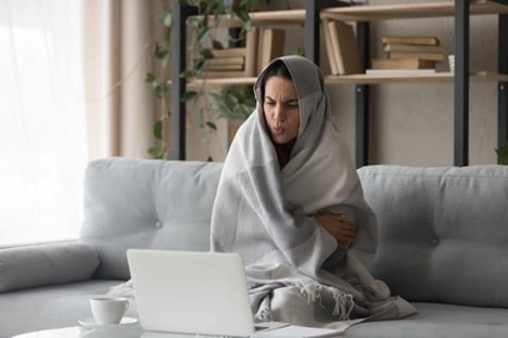 An image of someone who is cold at home due to a broken Furnace.