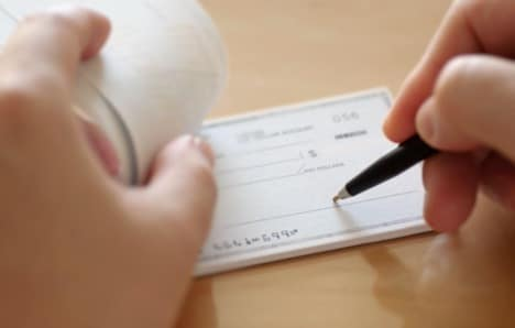 An image of a person writing a check